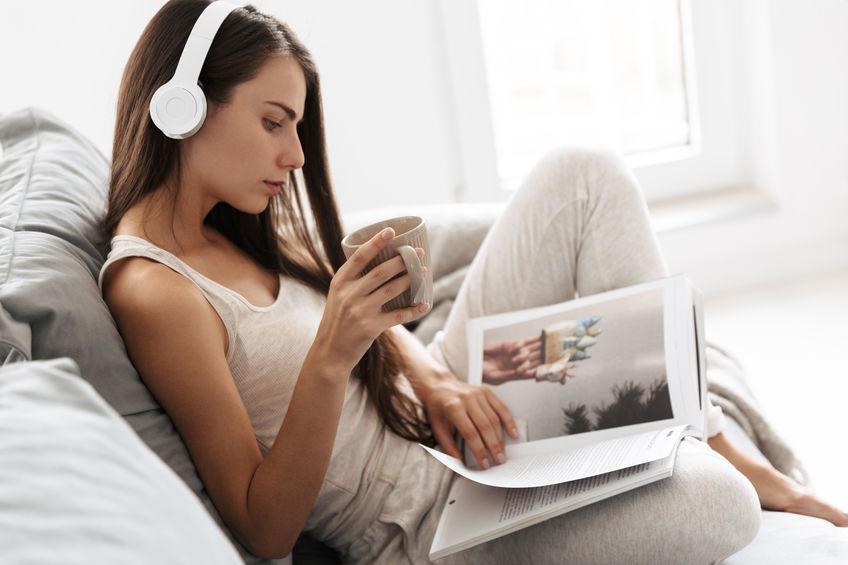 Mulher sentada em sofá com fone de ouvido e lendo