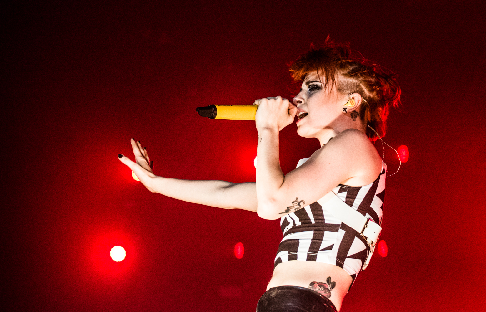 Hayley Williams cantando no palco segurando microfone