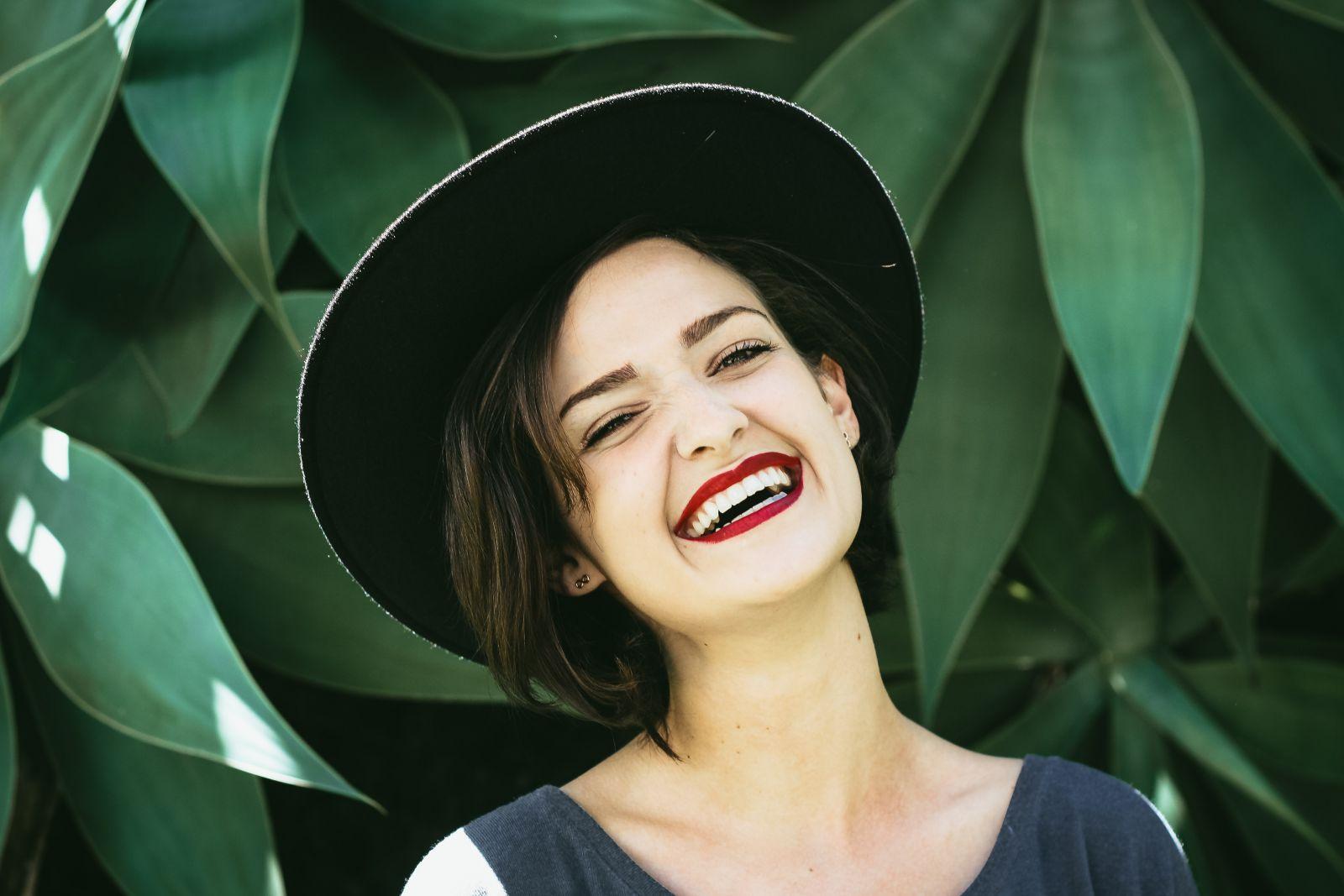Mulher sorrindo ao lado de uma planta
